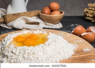 Eggs, dough, flour and rolling-pin on wooden table background. Preparation for making homemade ravioli pasta.