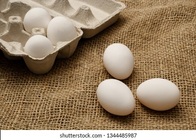 Eggs and egg carton on burlap sack cloth.