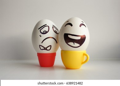 Eggs face. Cheerful company of eggs. Two eggs in mugs with coffee optimist and pessimist. Positive breakfast. Photo for your design