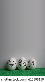 Eggs with faces photo for your design. With a place for text. Funny and cute. Three white eggs on a white wall background on a green grass cloth