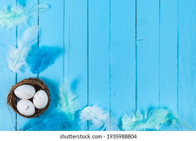 Eggs and feathers on a blue wooden background. Easter still life. - Shutterstock ID 1935988804