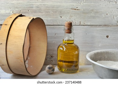 Eggs, flour and a bottle of olive oil on the white wooden table horizontal