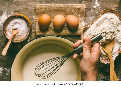 eggs, flour, and a male hand with a whisk dough top view.