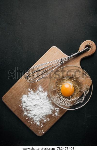 eggs and flour on dark background