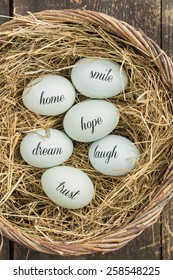Eggs with handwritten messages in a basket with straw