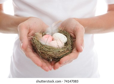 Eggs in a nest cupped in heart shaped hands.