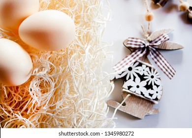 Eggs on the straw and wooden bunny background. Easter decorations.