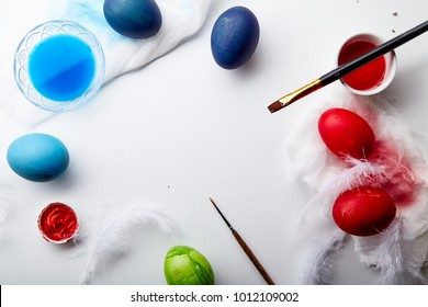 Eggs painted blue, green and red colors on Easter holiday. White background, copy space, framed composition