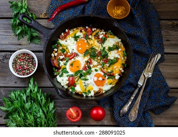 """Eggs poached with vegetables,named """"shakshouka"""" on wooden table."""