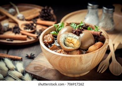 Eggs and pork boiled in the gravy on wooden table, Thai food.