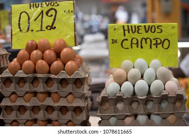 "Eggs for sale in Ecuadorian market.  Signs say ""Eggs, 12 cents,"" and ""Country Eggs."""