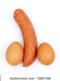 Eggs and sausage ordered like penis and testicles isolated on white