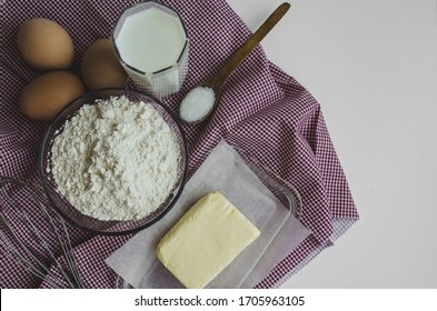 Eggs, sugar, milk, flour, butter, whisk, dish towel. Ingredients and tools for baking on the wooden table. Cooking and baking ingredients utensils on white background. Food accessories. Space for text