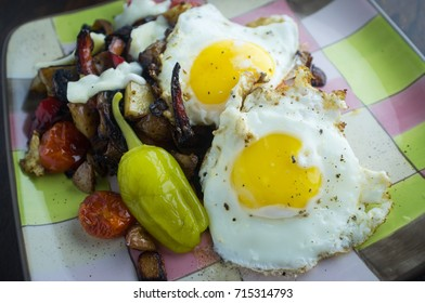 Eggs sunnyside up with pepperoncini and home fries