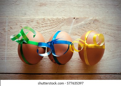 Eggs tied with color ribbon on the wooden table