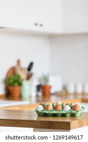 Eggs tray on wooden table white kitchen and kitchen accessories on background. Concept of food preparation.