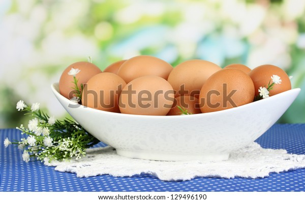 Eggs in white bowl on blue tablecloth close-up