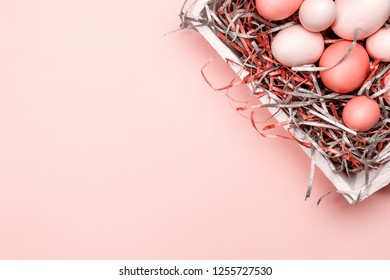 Eggs in a white tray. Creative Easter concept. Modern solid pink background. Horizontal. Living coral theme - color of the year 2019