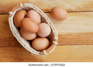 Eggs in wicker basket on wooden background top view