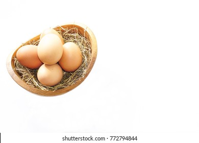 Eggs in a wooden bowl on a white background, copy space for text