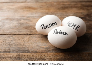 Eggs with words PENSION, RETIRE and 401k on wooden background. Space for text