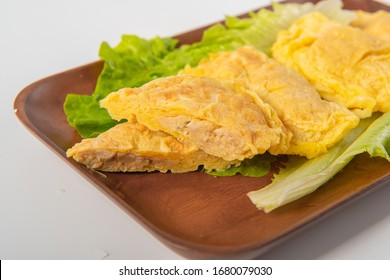 The eggs are wrapped in meat and lettuce is placed under them. They are packed in a wooden tray on a white background - Shutterstock ID 1680079030