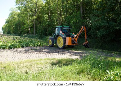 Egmond aan den Hoef, Netherlands, May 25, 2020. With the tractor the grass is cut on the slope of a ditch with a row of trees. On the edge of a field with ornamental onions.