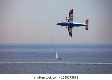 Egmont man Zee, Netherlands - July 19, 2017: an airplane of the dutch coastguard over the north sea with a sailboat and wind turbines in the background