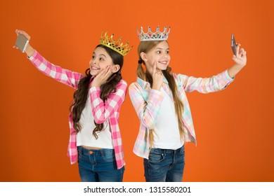 Egocentric princess. Kids wear golden crowns symbol princess. Warning signs of spoiled child. Avoid raising spoiled kids. Girls taking selfie photo smartphone camera. Spoiled children concept.