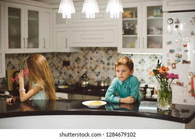 egoism concept little boy brother and small girl sister sitting separately indoors home kitchen