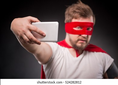 Egoist. Selfish. Hero. Super Hero. Picture of super hero man with red mask on making photos on mobile or smart phone in studio.