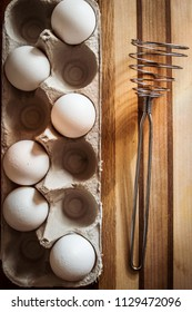 Egss and egg beater on wooden cutting board.