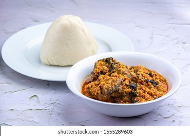 Egusi Soup and goat meat with Pounded yam on a white embossed background.