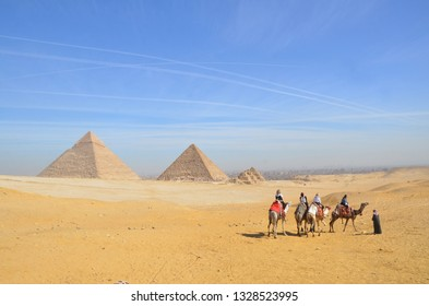 Egypt. Cairo - Giza. General view of pyramids from the Giza Plateau. Tourist riding camel crossing the desert.