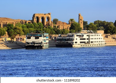 Egypt. Cruise ships docked at Kom Ombo on the Nile. The Temple of Sobek and Haroeris in background - seen colonnade of the Hypostyle Hall