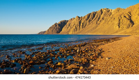Egypt, Dahab, mountains on sunset, sunrise and beach with stones, pebble, sea.
