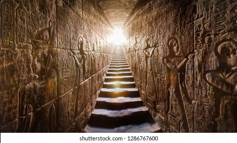 Egypt Edfu temple, Aswan. Passage flanked by two glowing walls full of Egyptian hieroglyphs, illuminated by a warm orange backlight from a door