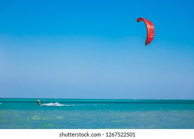 Egypt, Hurghada - 30 November, 2017: The kitesurfer with red kite gliding over the Red sea surface. Overwhelming marine scenery. The lone kiteboarder among the crystal clear water surface.