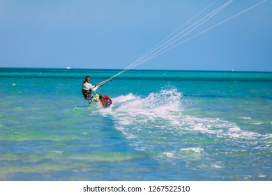 Egypt, Hurghada - 30 November, 2017: The kiteboarder gliding over the Red sea surface. The professional surfer on the board holding the kite straps. The wave riding. Amazing marine landscape.