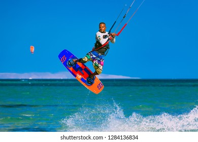 Egypt, Hurghada - 30 November, 2017: The kitesurfer soaring in the blue sky over the Red sea surface. Amazing wave splash. The extreme water sport activity. Popular tourist attraction.