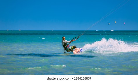 Egypt, Hurghada - 30 November, 2017: The kitesurfer gliding on the Red sea waves. Extreme outdoor activity. The lone man in the sport equipment riding on the water surface. Stunning marine scene.