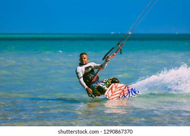 Egypt, Hurghada - 30 November, 2017: Close-up kitesurfer standing on the surfboard. Red sea background. The kiteboarding as the popular water sport activity. The wave riding. Breathtaking marine scene