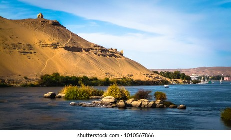 Egypt. The Nile at Aswan and the West Bank with Tombs of the Nobles (from the Old and Middle Kingdom). There is Qubbet el-Hawa - 'Dome of the Winds' (tomb of a Muslim prophet) at the crest of the hill
