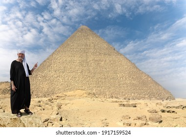 An Egyptian in a black robe and a turban stands in front of the huge Cheops pyramid in Giza. He stands on a stone and points with one finger at the monument.