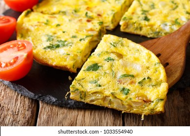 Egyptian cuisine: omelet Igga with greens, onions and tomatoes close-up on the table. horizontal