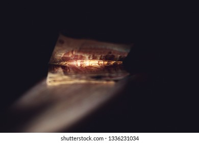 Egyptian currency, crumpled bill lying on the surface in the dark illuminated by a ray of light