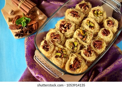 Egyptian dessert Kunafa made of kataifi dough with pistachio and pecan nuts in a glass baking dish. Top view