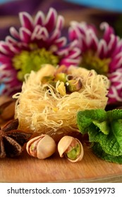 Egyptian dessert Kunafa made of kataifi dough with pistachios surrounded by spices, flowers and nuts