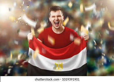 An Egyptian fan, a fan of a man holding the national flag of Egypt in his hands. Soccer fan in the stadium.