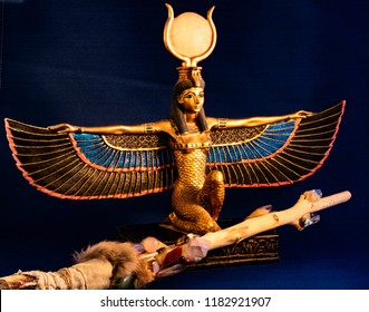 Egyptian goddess Isis kneeling with traditional magic wand made with quartz, amethyst crystals, wood and feathers